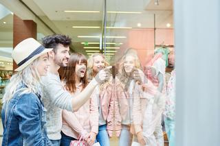 Freunde vor Schaufenster eines Modeladen