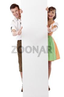 Junges glückliches Paar steht hinter Werbefläche mit Daumen nach oben. Freigestellt auf weissem Hintergrund.