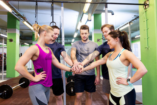 group of friends holding hands together in gym