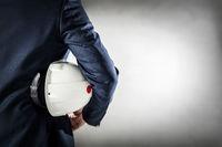 Businessman holding white safety helmet.