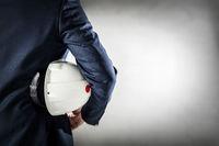 Businessman holding white safety helmet.