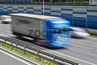 Large goods vehicle moving at full speed on six lane controlled-access highway.