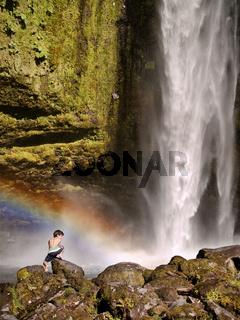 Waterfall with rainbow and boy