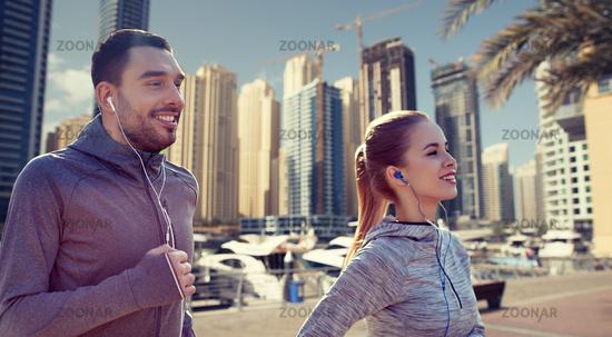 happy couple with earphones running in city