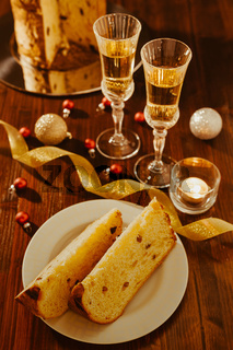 Sliced italian panettone, sparkling wine and decorations over a table