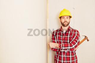 Zimmermann mit Hammer und Schutzhelm