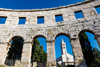 White Church Framed in the Arch of Ancient Roman Amphitheater in Pula, Istria, Croatia