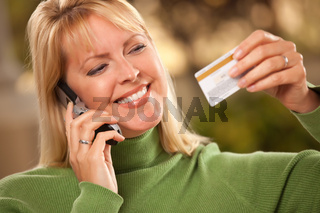 Cheerful Smiling Woman Using Her Phone with Credit Card in Hand.