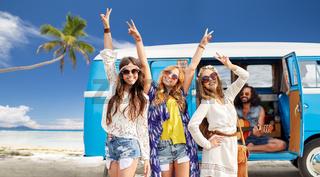 happy hippie friends at minivan car on beach