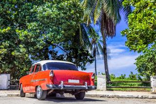 HDR - Roter amerikanischer Oldtimer mit weissem Dach parkt unter blauem Himmel in Varadero Kuba - Se