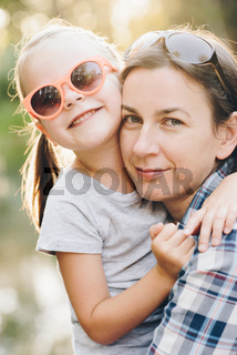 mother and her charming little daughter are hugging and smiling