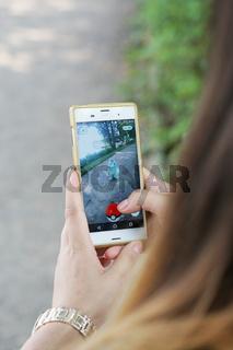 girl playing Pokemon Go on her smartphone