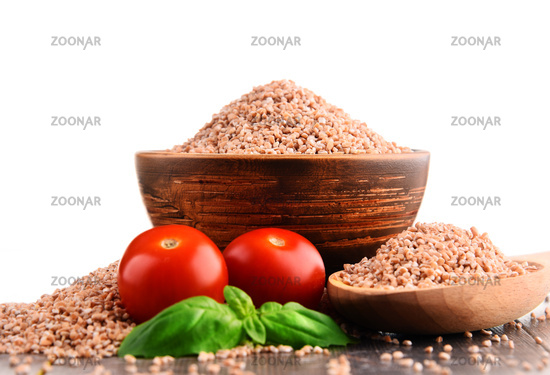 Bowl of uncooked spelt isolated on white background