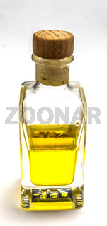 Semi-filled bottle with a yellow liquid and a cork stopper in front of a white background