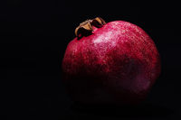 Close-up photo of the pomegranate on black background isolated
