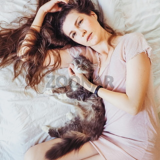 Beautiful woman lying in bed with her charming cat