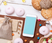 Mock-up of smartphone among sweets