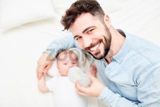 Stolzer Vater füttert Baby mit Milch
