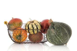 Orange and green pumpkins in basket