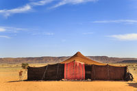 A tent made of camel skin in desert with mountains on background