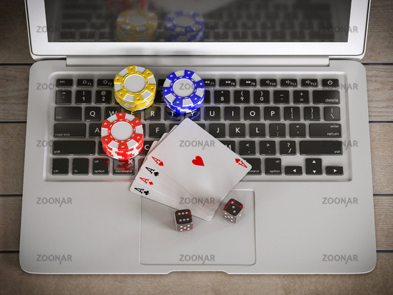 laptop with chips, dices and poker cards