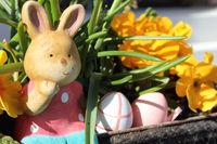 Osterhase mit bunten Eiern und Blumen
