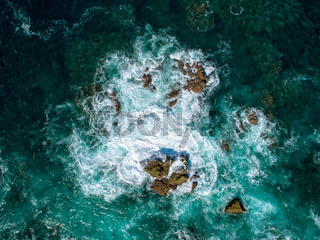 Aerial View of Waves Breaking on Rock