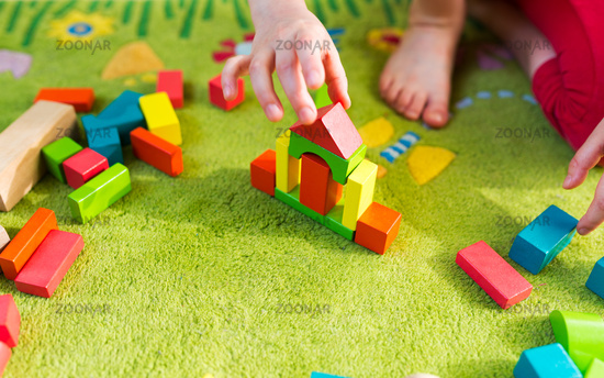 Small child playing with wooden blocks on green carpet