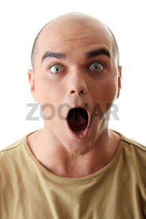 Closeup portrait of a shocked young man looking straight on a white background
