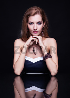 Young beautiful blonde woman sitting at mirror table on black background