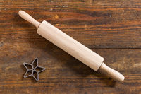 Nudelholz und Stern als Backform auf verwittertem Holz
