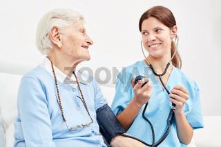 Pflegekraft macht Blutdruckmessung bei Seniorin