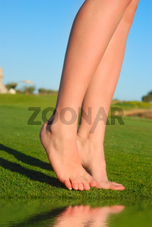 beautiful female legs on grass near lake