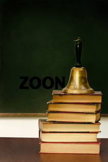 Stack of books and school bell on desk