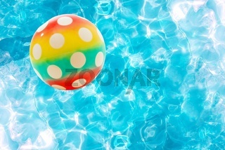 Colorful ball over a bright swimming pool