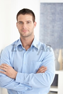 Casual man standing arms crossed smiling