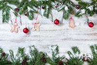 Snowy Christmas branches with associated ornaments on rustic white wooden background
