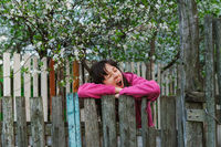 young woman standing by old fence and yawn