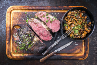Barbecue wagyu roast beef with chanterelle as top view on a cutting board