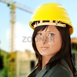 Young female architect or builder wearing a yellow hart hat