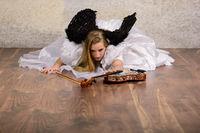 Junge blonde Frau im Brautkleid mit schwarzen Flügeln auf dem Boden und greift nach einer Geige