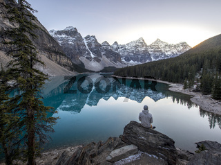 Young man sitting on a rock overlooking  beautful mountain lake