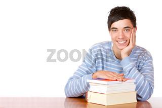 Hübscher fröhlicher Student  mit Büchern sitzt am Tisch