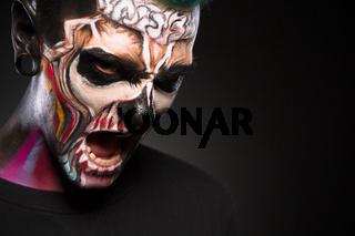 Monster makeup, man with zombie face, studio portrait.