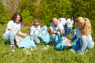 volunteers with garbage bags cleaning park area