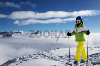 Young skier at top of snowy mountains at sun winter day