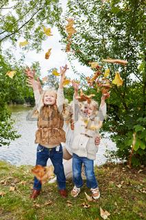 Aktive Kinder werfen Blätter in die Luft