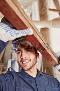 Schreiner Lehrling trägt Holz