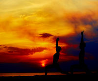 Yoga people training and meditating in warrior pose outside by beach at sunrise or sunset.