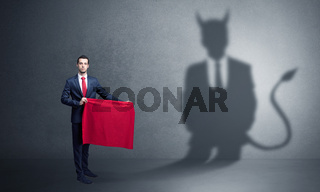 Businessman with devil shadow and toreador concept